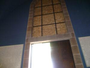 Ausgang der Friedenskirche Kassel, statt des Buntglasfensters sitzt dort nun eine Spanplatte
